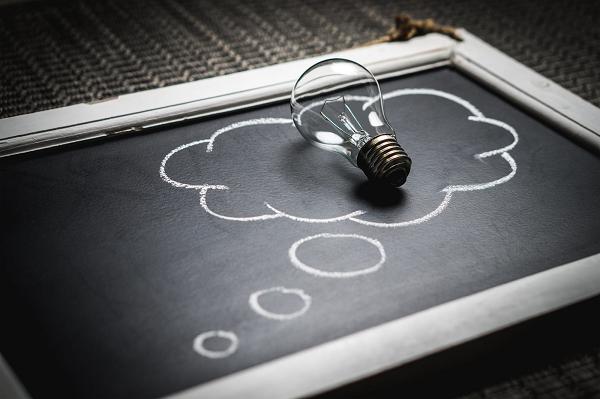 a lightbulb in an ideas cloud on a blackboard