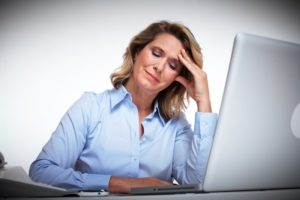Business woman having a headache trying to resolve debt problems.
