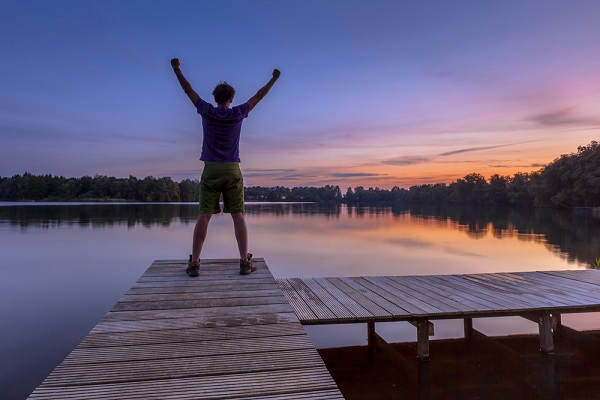 man holding arms in air towards a sunset - a blog post about life after an iva