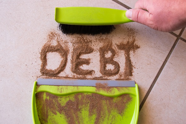 the word debt writtien in sand being swept away - vulnerability and debt concept