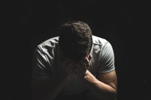 man holding head in his hands - a blog post about problem debt