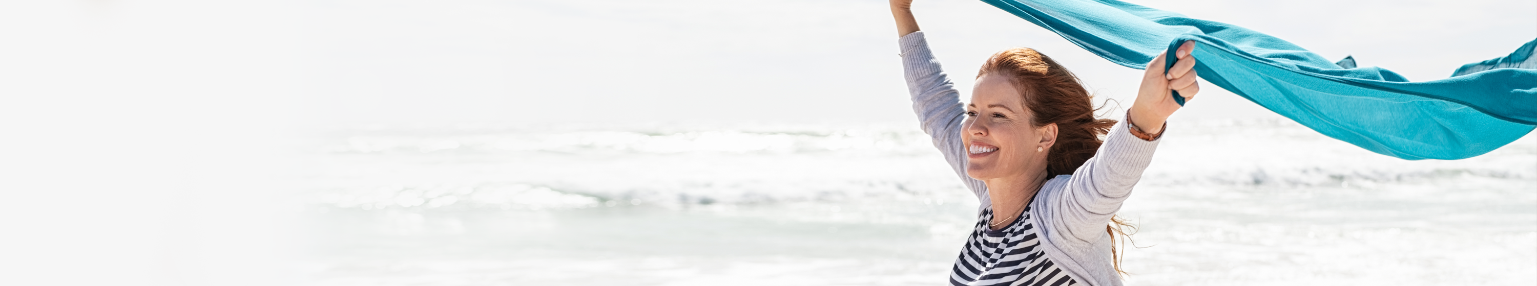 Lady running on the beach with hands in the air
