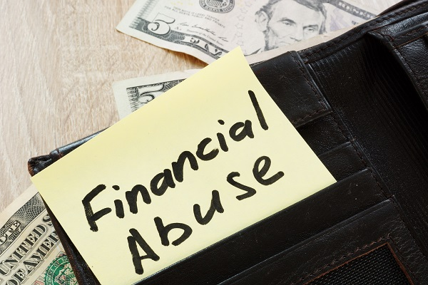 financial abuse written on a note with money surrounding it, financial abuse signs